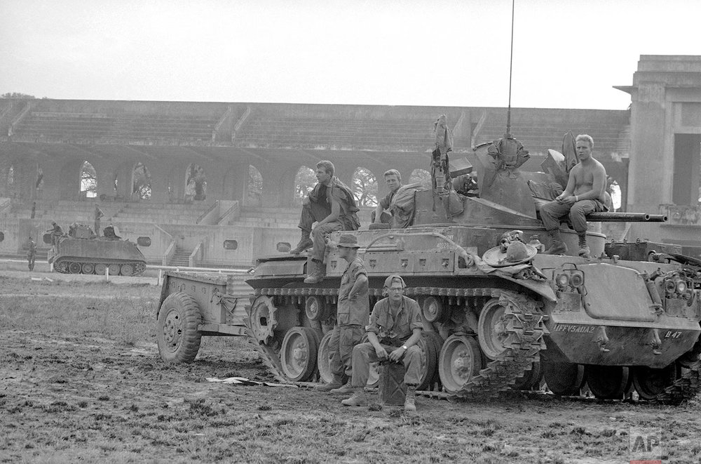 US soldiers rest on top of a tank at the Phu Tho racetrack in western Saigon, Feb. 8-26, 1968. US and S.Vietnamese troops set up a fire support base at the track to support troops engaged in mop-up operations throughout the city during the Tet Offensive. (AP Photo/Eddie Adams)