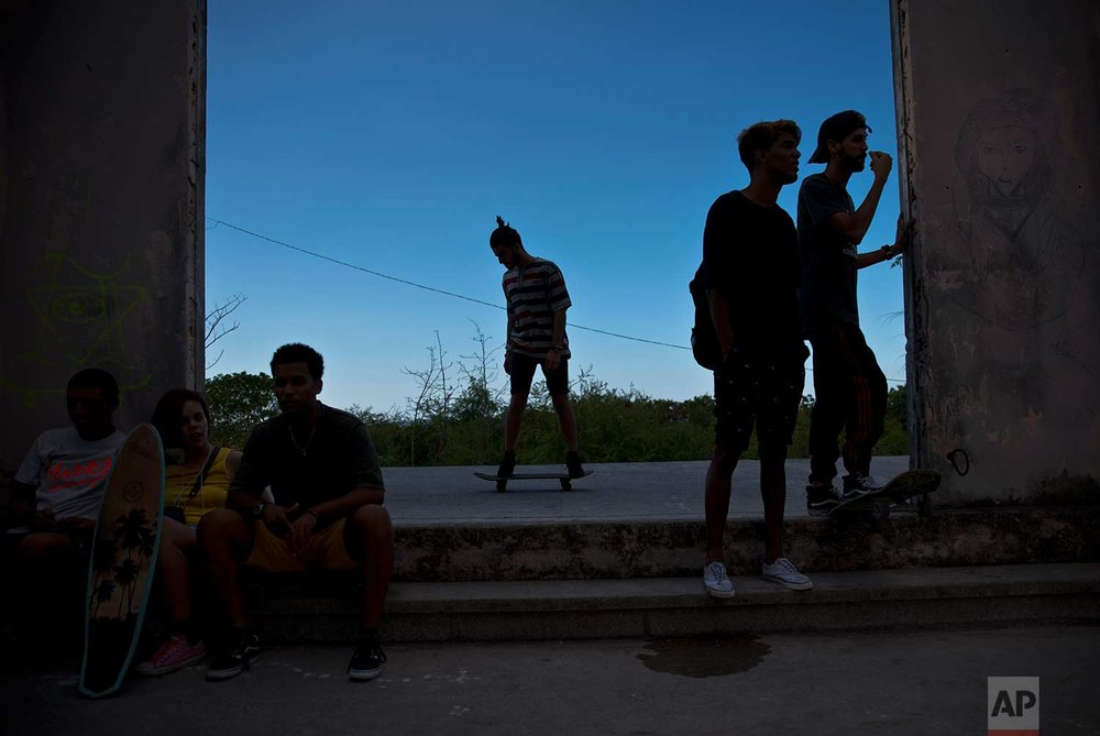 In this Jan. 11, 2018 photo, a skater rolls by as others rest inside an abandoned gym that was converted into a recreational space for skateboarders, the day of its inauguration inside the Educational complex Ciudad Libertad, a former military barracks that the late Fidel Castro turned into a school complex after the revolution, as the sun sets in Havana, Cuba. (AP Photo/Ramon Espinosa)
