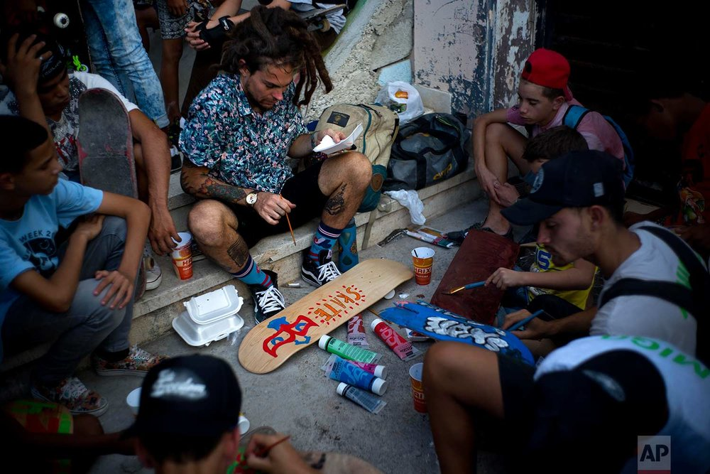 In this Jan. 11, 2018 photo, Canadian skater Chris Dyer paints a skateboard inside an abandoned gym that was converted into a recreational space for skateboarders, the day of its inauguration inside the Educational complex Ciudad Libertad, a former military barracks that the late Fidel Castro turned into a school complex after the revolution in Havana, Cuba. (AP Photo/Ramon Espinosa)