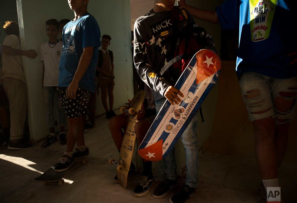 In this Jan. 11, 2018 photo, a skater carries a new Cuban flag motiffed skateboard, donated by Humanity Stoked, during the inauguration of a new recreational space for skateboarders, created out of an abandoned gym at the Educational complex Ciudad Libertad, a former military barracks that the late Fidel Castro turned into a school complex after the revolution in Havana, Cuba. (AP Photo/Ramon Espinosa)