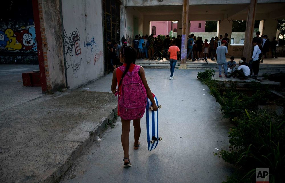 In this Jan. 11, 2018 photo, a young girl carries her Cuba flag motif skateboard to the inauguration ceremony of a new recreational space for skateboarders, created in an abandoned gym at the Educational complex Ciudad Libertad, a former military barracks that the late Fidel Castro turned into a school complex after the revolution in Havana, Cuba. (AP Photo/Ramon Espinosa)