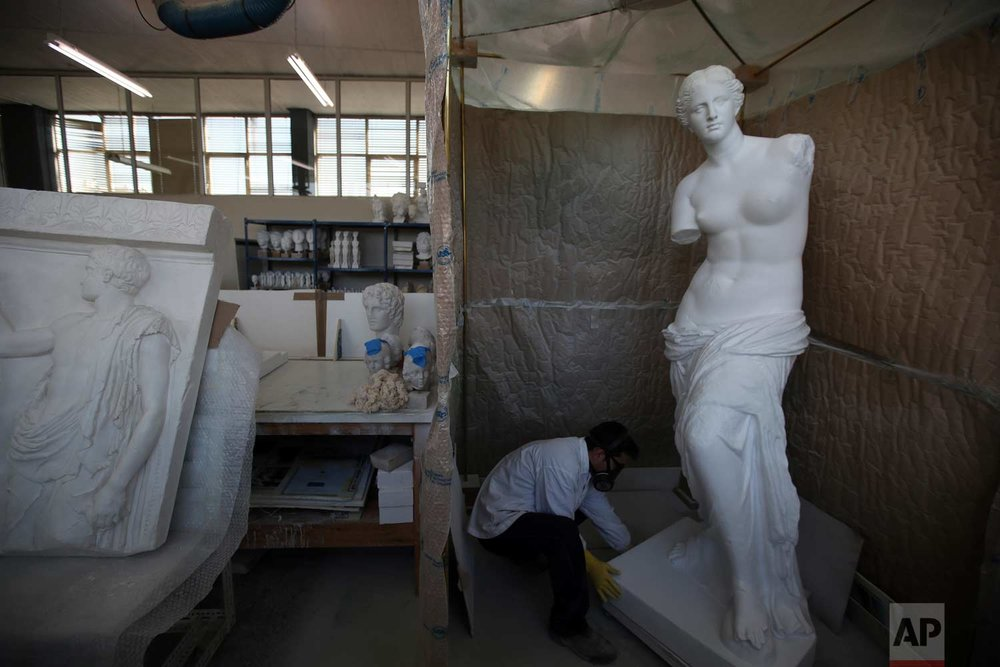 In this Tuesday, Jan. 16, 2018, a copy of Venus de Milo, Aphrodite the ancient Greek goddess of love, beauty, pleasure and procreation, made by plaster goes through color processing in Culture Ministry's Lab in Athens.  (AP Photo/Thanassis Stavrakis)