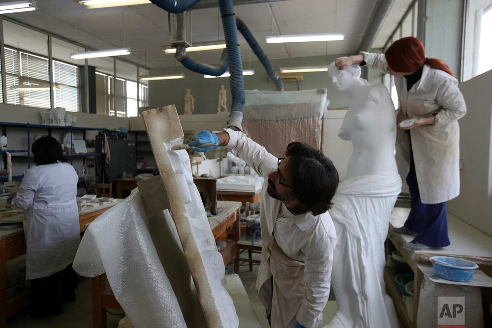 In this Wednesday, Jan. 24, 2018, sculptors work in the Culture Ministry's Lab in Athens.  (AP Photo/Thanassis Stavrakis)