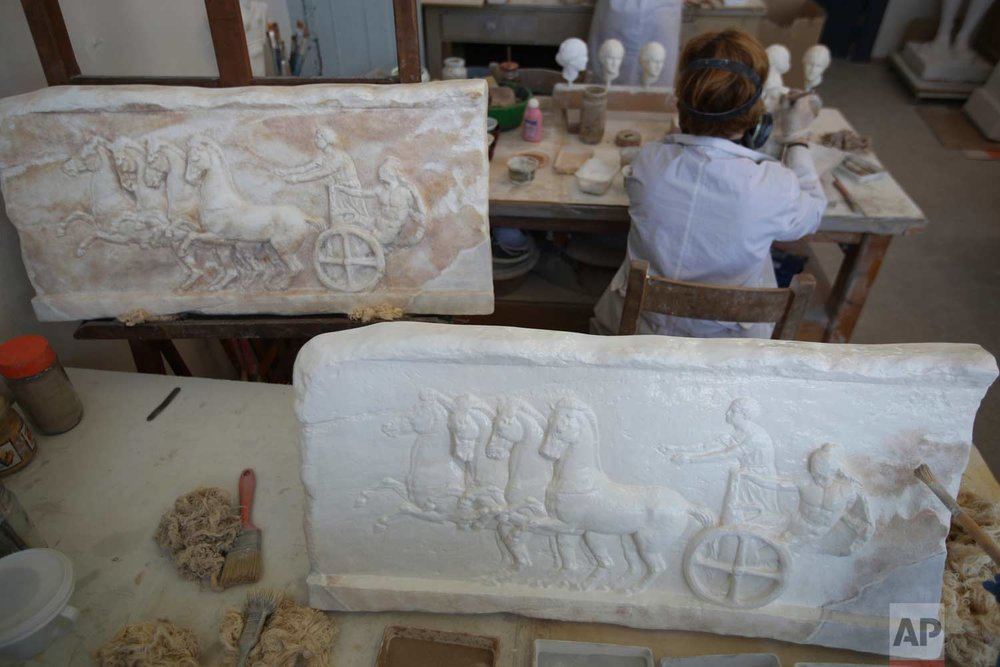 In this Monday, Jan. 22, 2018, painters work on plaster replicas in the Culture Ministry's Lab in Athens. The team of about 50 fine arts graduates work on a range of sculptures, from a three-inch hare from Roman-era Macedonia to a seven-foot statue of Zeus, or Poseidon, made in the mid-5th century B.C. and one of the star exhibits of the National Archaeological Museum in Athens. (AP Photo/Thanassis Stavrakis)