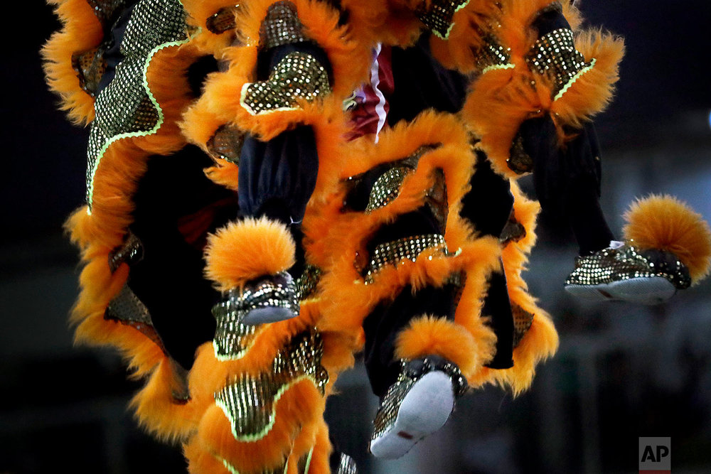 In this Friday, Feb. 2, 2018, photo, members of a lion dance troop in Singapore are airborne as they compete in the 11th International Lion Dance Competition in Singapore. (AP Photo/Wong Maye-E)