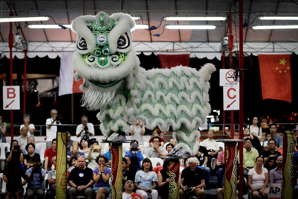 In this Friday, Feb. 2, 2018, photo, spectators watch as members of a lion dance troop from Indonesia compete in the 11th International Lion Dance Competition in Singapore. (AP Photo/Wong Maye-E)