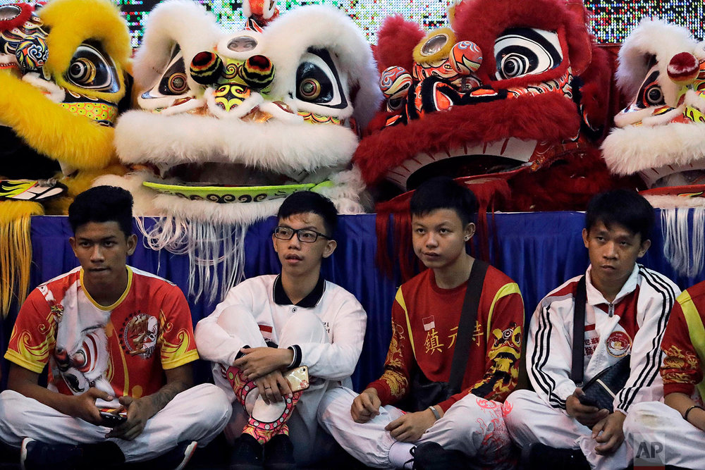 In this Friday, Feb. 2, 2018, photo, competitors sit in front of lion costumes as they watch fellow competitors perform during the 11th International Lion Dance Competition in Singapore. (AP Photo/Wong Maye-E)