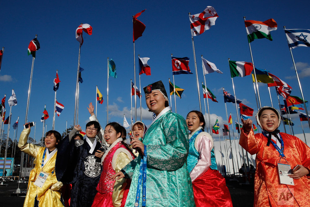 A group of volunteers wearing handbook, Korean traditional dress, greet athletes entering the Olympic Village as flags including North Korea's, fly prior to the 2018 Winter Olympics in Gangneung, South Korea, Thursday, Feb. 1, 2018. (AP Photo/Jae C. Hong)