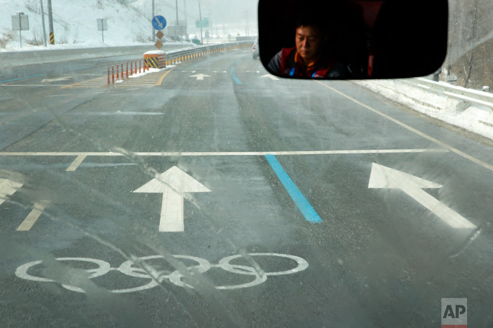 A bus driver travels to the Phoenix Snow Park in an Olympic lane at the 2018 Winter Olympics in Pyeongchang, South Korea, Saturday, Feb. 3, 2018. The venue will host freestyle skiing and snowboarding events. (AP Photo/Charlie Riedel)