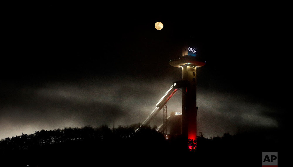 The waning moon rises beyond the Alpensia Ski Jumping Center at the 2018 Winter Olympics in Pyeongchang, South Korea, Friday, Feb. 2, 2018. (AP Photo/Charlie Riedel)