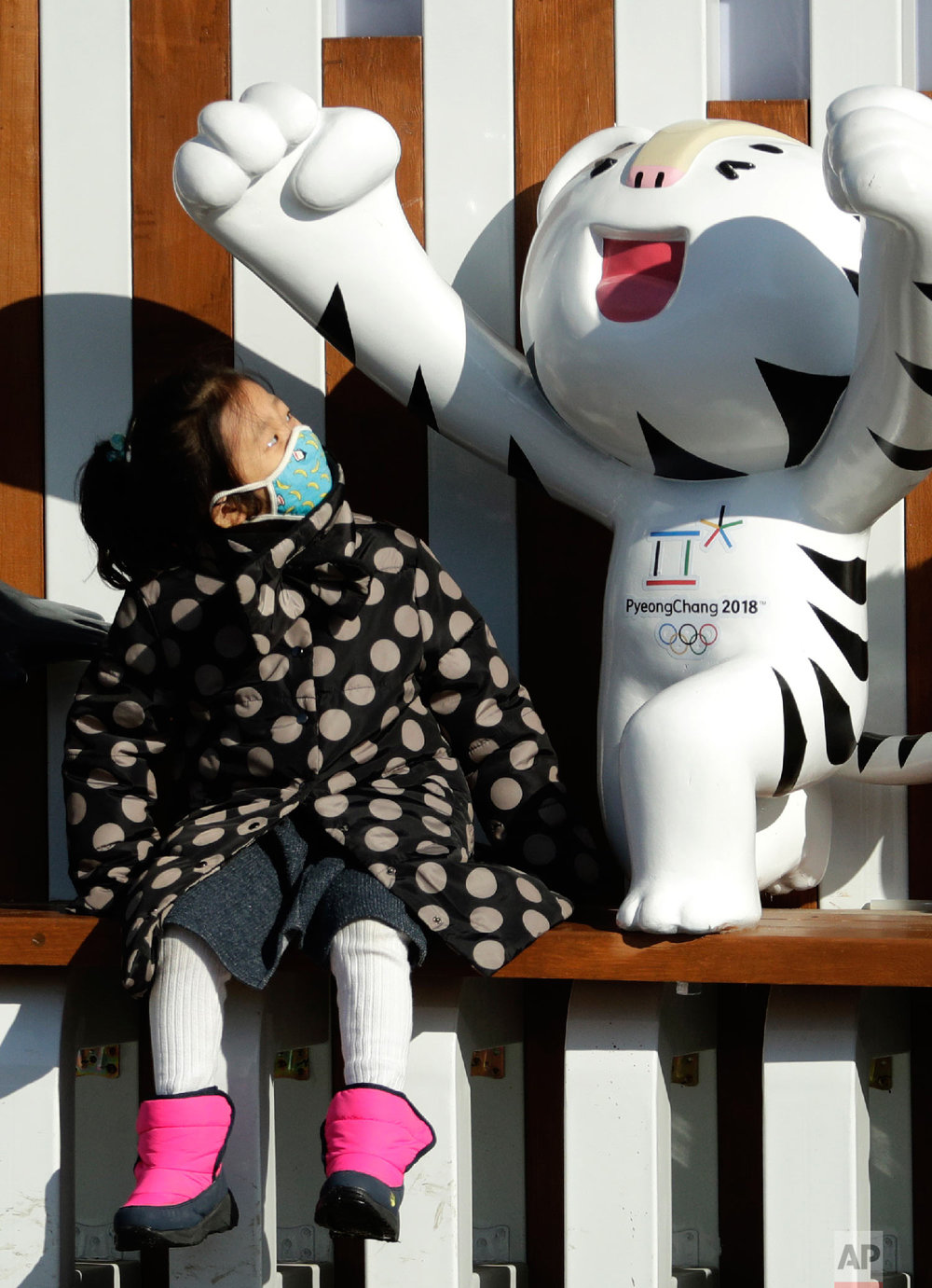 A young girl looks at an Olympic mascot at the Pyeongchang Olympic Plaza as preparations continue for the 2018 Winter Olympics in Pyeongchang, South Korea, Sunday, Feb. 4, 2018. (AP Photo/Charlie Riedel)