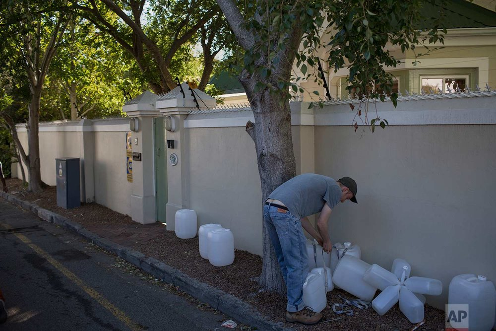 A Cape Town resident sorts out his containers as he arrives at a source of natural spring water in the city on Thursday, Feb. 1, 2018. (AP Photo/Bram Janssen)