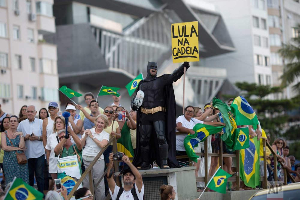 "A demonstrator dressed as Batman holds a sign that reads in Portuguese ""Lula in Prison"" during a protest against former president Luiz Inacio Lula da Silva on Copacabana beach, in Rio de Janeiro, Brazil, Tuesday, Jan. 23, 2018. (AP Photo/Silvia Izquierdo)"