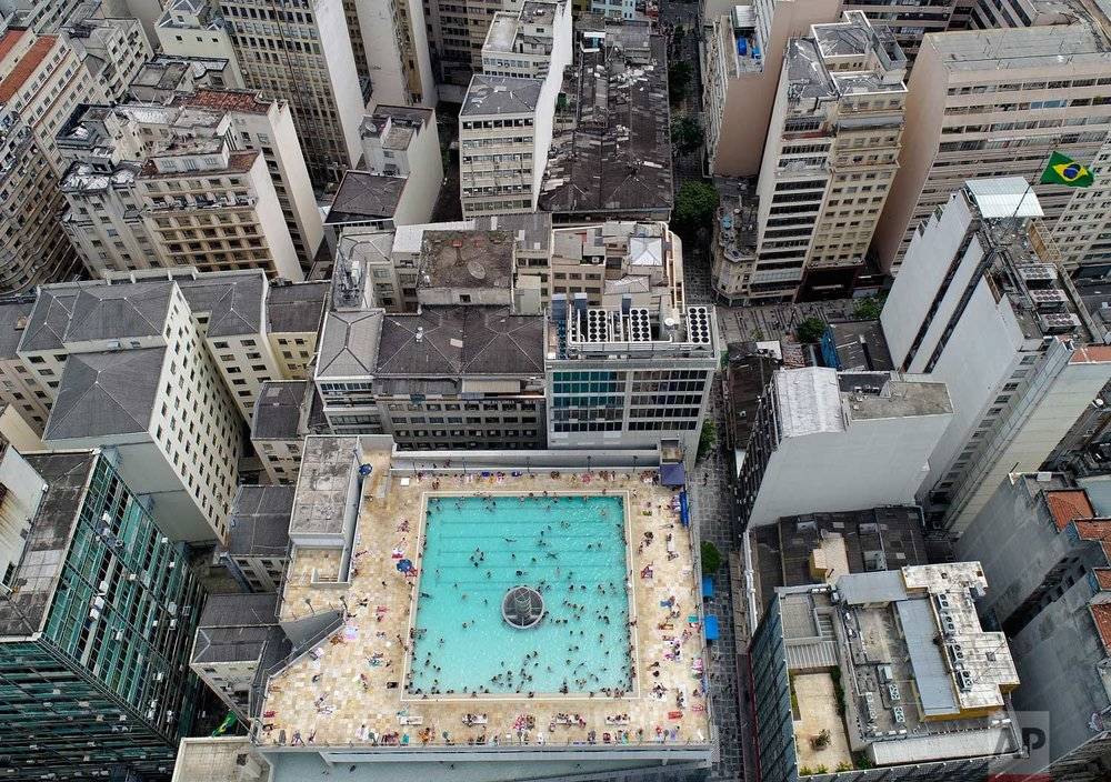 Visitors swim in a rooftop pool at Sesc 24 de Maio, a cultural and sports center owned by the Commerce and Industries of the Sao Paulo State, in downtown Sao Paulo, Brazil, Thursday, Jan. 25, 2018. (AP Photo/Andre Penner)