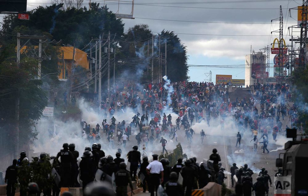 Soldiers and police launch tear gas at demonstrators marching to the National Stadium to protest the presidential inauguration of Juan Orlando Hernandez, in Tegucigalpa, Honduras, Saturday, Jan. 27, 2018.  (AP Photo/Eduardo Verdugo)