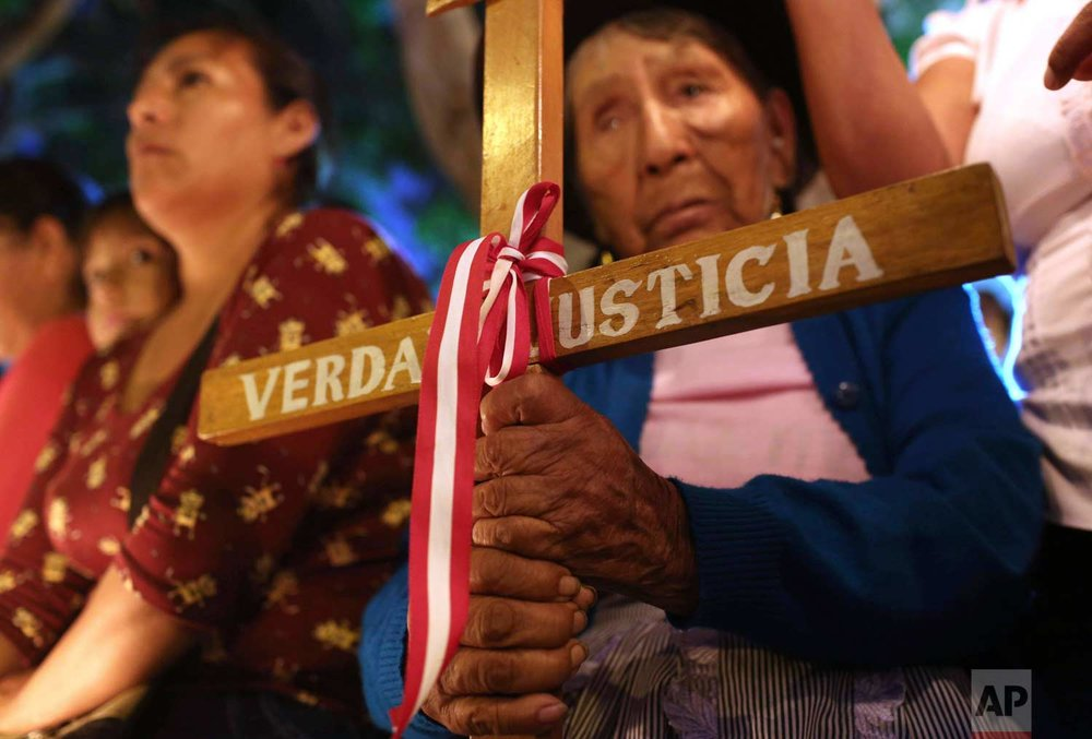 Relatives of victims executed by a clandestine group of soldiers during the government of former president Alberto Fujimori attend a vigil in Lima, Peru, Thursday, Jan. 25, 2018. (AP Photo/Martin Mejia)