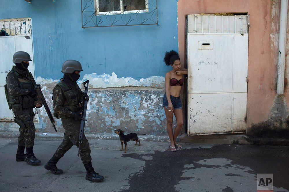 In this Jan. 18, 2018 photo, a woman stands in a doorway smoking a cigarette as soldiers take part in a surprise operation in the Jacarezinho slum in Rio de Janeiro, Brazil.  (AP Photo/Leo Correa)