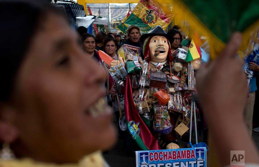 People accompany the statue of Ekeko, the Bolivian god of prosperity and the central figure of the Alasita miniature fair, in La Paz, Bolivia, Tuesday, Jan. 23, 2018. (AP Photo/Juan Karita)