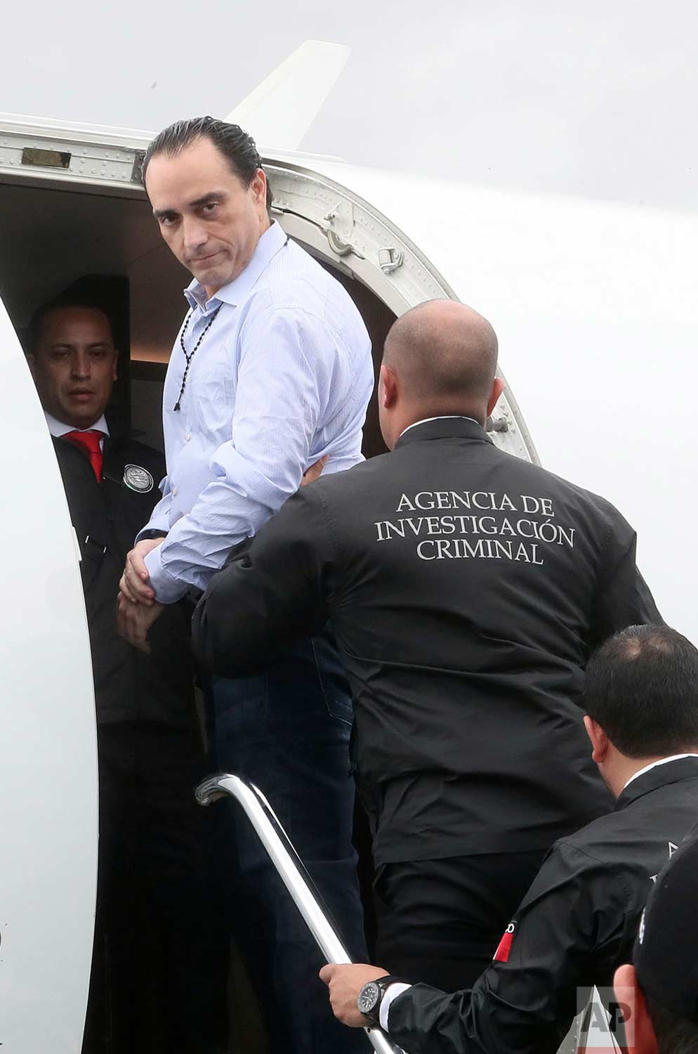 In this Thursday, Jan. 4, 2018 photo released by the Panama Foreign Ministry, Mexico's former Quintana Roo state Gov. Roberto Borge looks over his shoulder as he is escorted onto a Mexican plane in Panama City. (Efren Giron/Panama Foreign Ministry via AP)