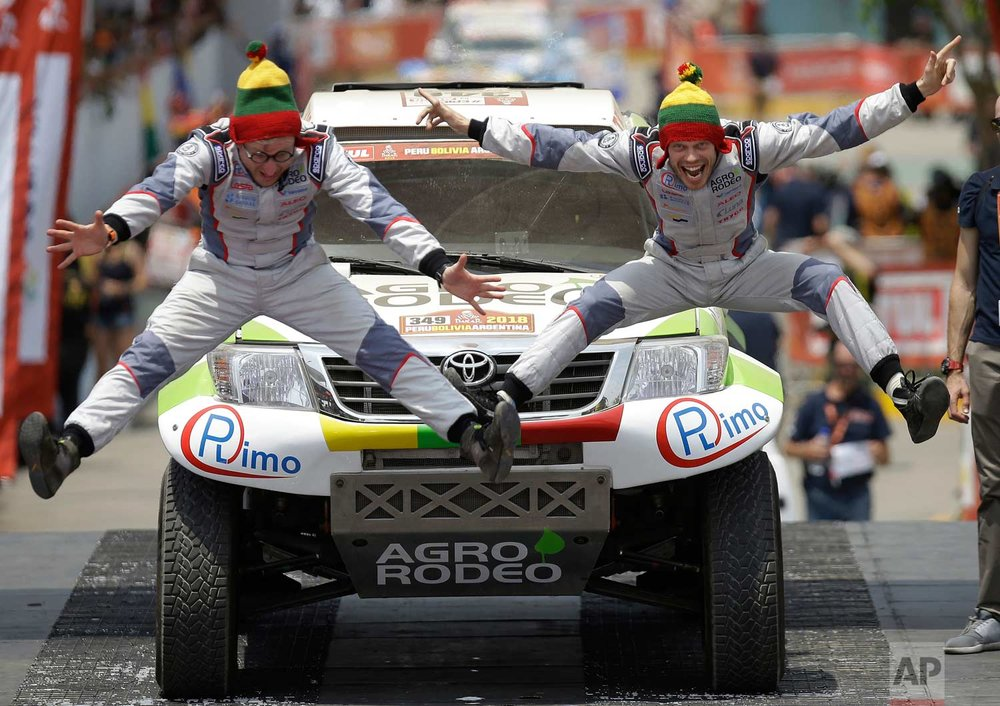 In this Jan. 6, 2018 photo, Zala Vaidotas, right, and his co-driver Jurgelenas Saulius, both of Lithuania, jump in unison on the podium ramp during the Dakar Rally ceremonial start, in Lima, Peru. (AP Photo/Martin Mejia)