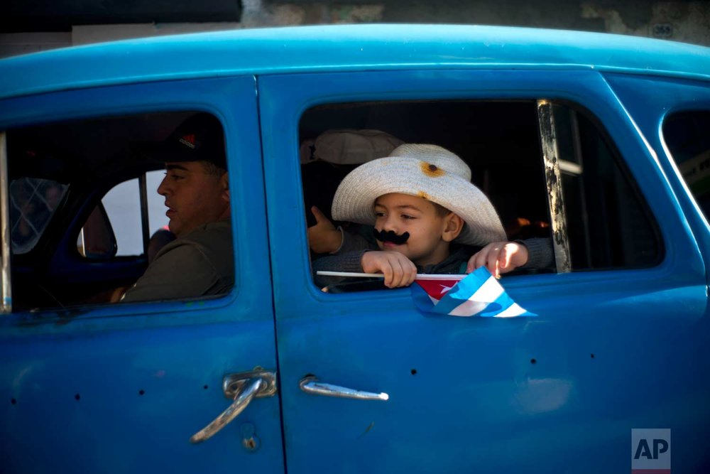 "In this Jan. 8, 2018 photo, a boy dressed as a ""Guajiro"" travels in a vintage American car during a caravan marking the 59th anniversary of the arrival of Fidel Castro and his rebel army in Regla, outskirts of Havana, Cuba. (AP Photo/Ramon Espinosa)"