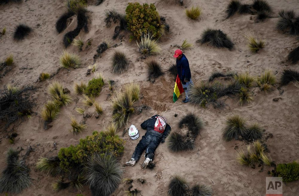 In this Saturday, Jan. 13, 2018 photo, a spectator checks on Guillaume Martens after the Macad Rally Team rider was overcome with fatigue and had no option but to retire, during stage 7 of the 2018 Dakar Rally between La Paz and Uyuni, Bolivia. (Franck Fife/Pool Photo via AP)