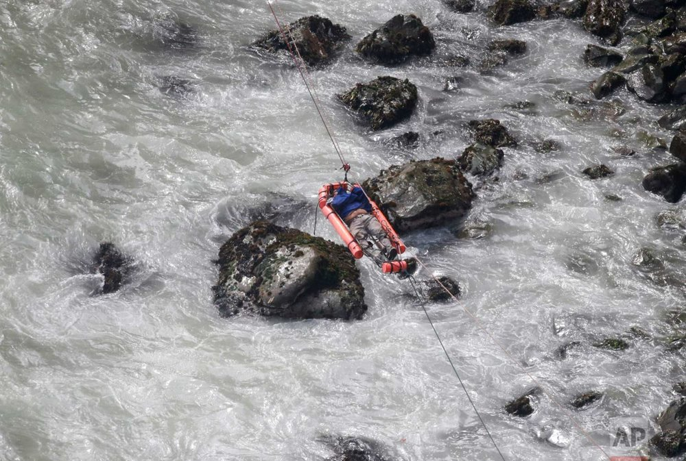 In this photo provided by the government news agency Andina, an injured man is transported over water from a bus that fell off a cliff after it was hit by a tractor-trailer rig, in Pasamayo, Peru, Tuesday, Jan. 2, 2018. (Vidal Tarky, Andina News Agency via AP)