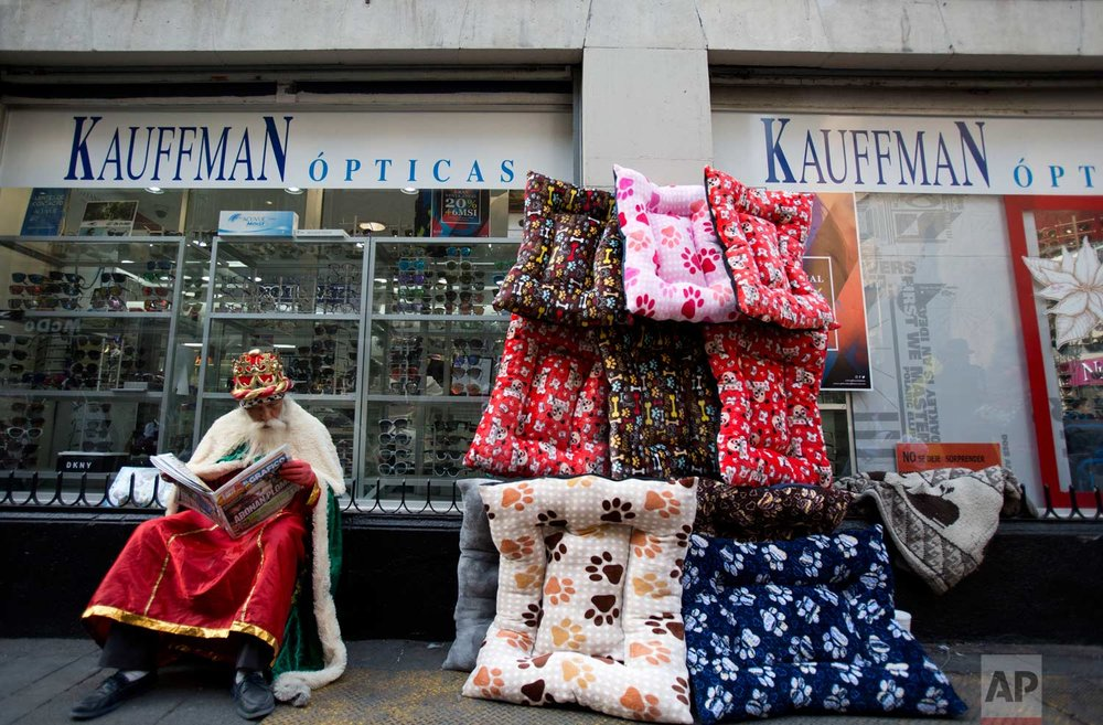 Performance artist Roberto Martinez Perez, dressed as one of the Three Kings, reads a newspaper while waiting for families wanting to pose for souvenir photos on the eve of the Epiphany, in the historic center of Mexico City, Friday, Jan. 5, 2018. (AP Photo/Rebecca Blackwell)