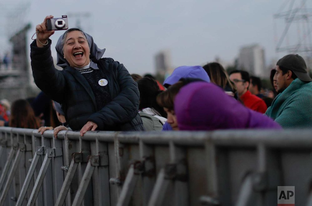 A nun takes a picture as she waits for Pope Francis to celebrate Mass at O'Higgins Park in Santiago, Chile, Tuesday, Jan. 16, 2018. (AP Photo/Natacha Pisarenko)