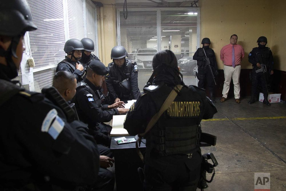 In this Saturday, Jan. 13, 2018 photo, lawmaker Julio Juarez Ramirez, right, stands handcuffed in a courtroom flanked by two police officers, in Guatemala City. Authorities in Guatemala arrested Juarez Ramirez accused of orchestrating the murder of two journalists in 2015. (AP Photo/Moises Castillo)