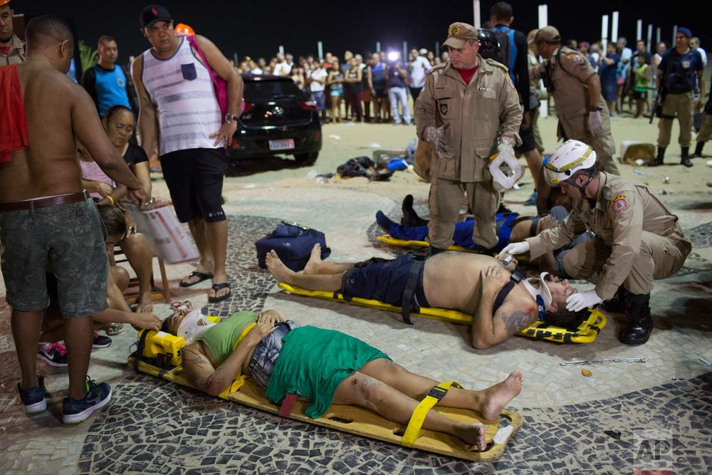 Firefighters give the first aid to people that were hurt after a car drove into the crowded seaside boardwalk along Copacabana beach in Rio de Janeiro, Brazil, Thursday, Jan. 18, 2018. (AP Photo/Silvia Izquierdo)