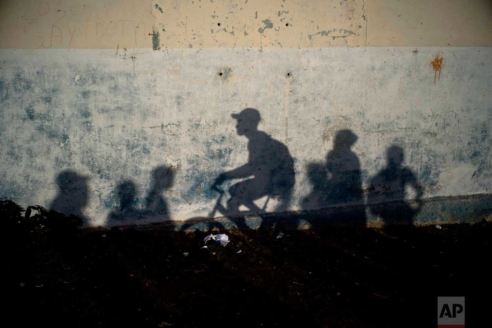 In this Jan. 22, 2018 photo, people's shadows are cast on a wall at sunset in the neighborhood of Chicharrones in Santiago, Cuba. (AP Photo/Ramon Espinosa)