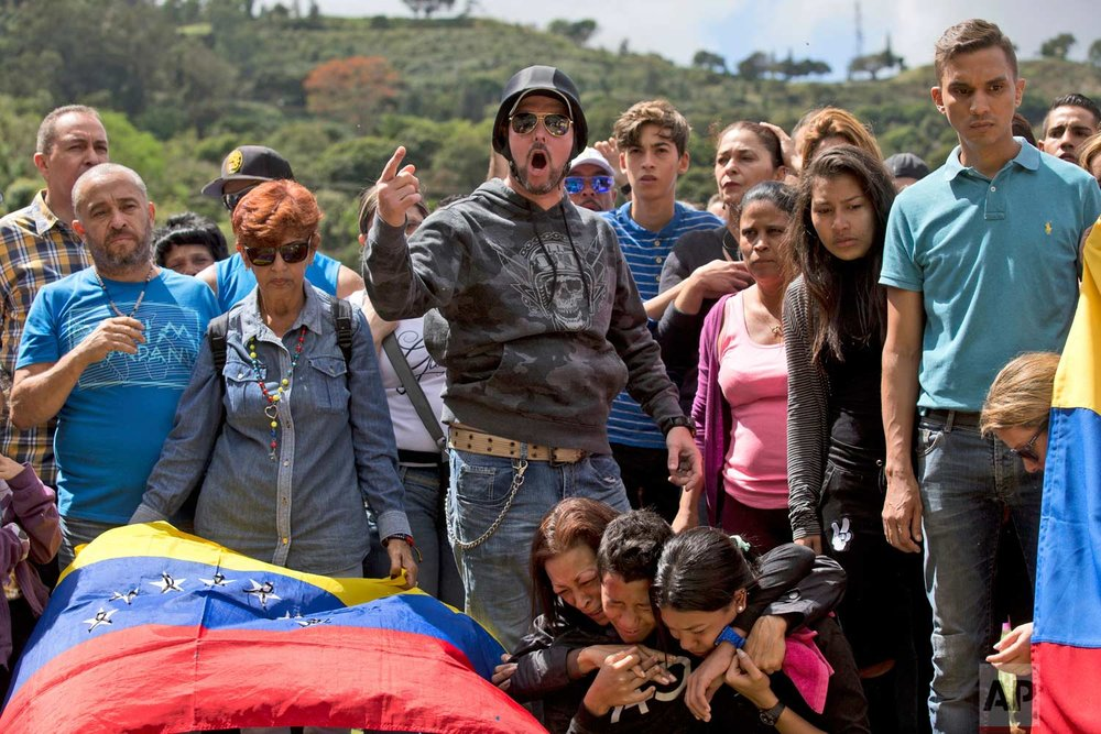 Friend and relatives of Jose Diaz Pimentel shout slogans against the government of Venezuelan President Nicolas Maduro during his funeral service at a cemetery in Caracas Venezuela, Saturday, Jan. 20, 2018. (AP Photo/Fernando Llano)