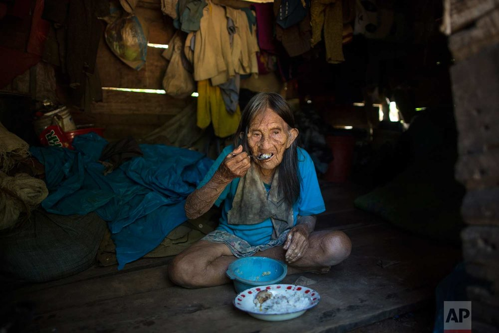 Maria Naji, 85, eats rice and fish caught by her son, in the village of Palma Real, Madre de Dios province, Peru, Wednesday, Jan. 17, 2018. (AP Photo/Rodrigo Abd)