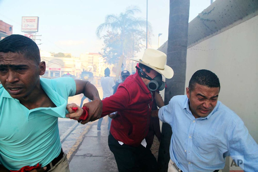 In this Friday, Jan. 12, 2018 photo, the former President of Honduras Jose Manuel Zelaya is pulled to safety after military police launched tear gas at protesters, near the presidential house in Tegucigalpa, Honduras. (AP Photo/Fernando Antonio)