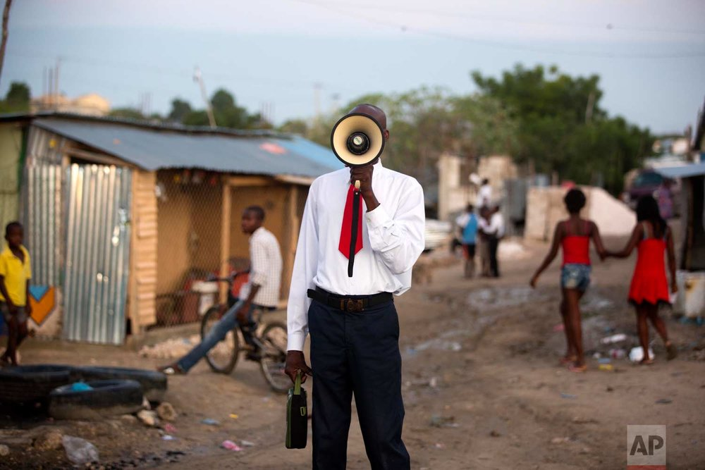 In this Sunday, Jan. 7, 2018 photo, a bullhorn preacher evangelizes to the passing residents of the Caradeux refugee camp set up nearly eight years ago for people displaced by the 2010 earthquake, in Port-au-Prince, Haiti. (AP Photo/Dieu Nalio Chery)