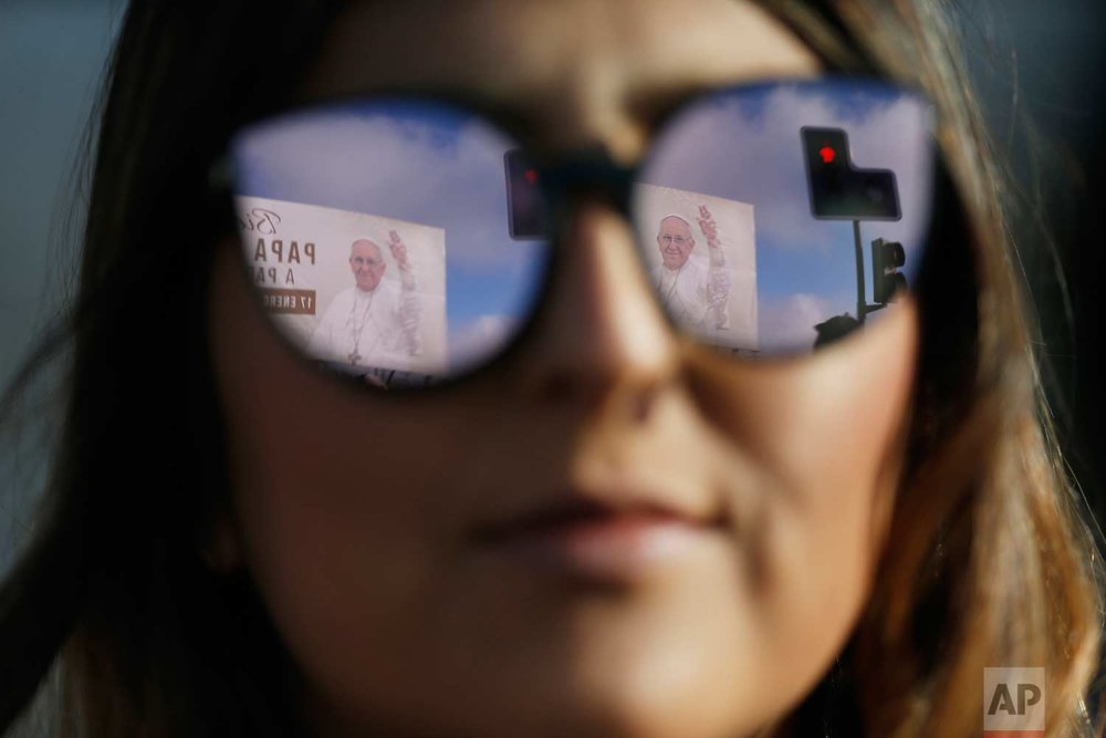 A banner welcoming Pope Francis is reflected in a woman's sunglasses as she waits for the pope's arrival at the Maquehue Air Base, in Temuco, Chile, Wednesday, Jan. 17, 2018.  (AP Photo/Luis Hidalgo)