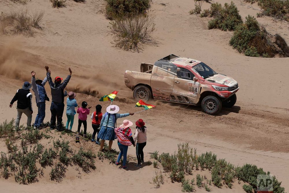 In this Sunday, Jan. 14, 2018 photo, spectators cheer as Driver Giniel De Villiers, of South Africa, and co-driver Dirk Von Zitzewitz, of Germany, race their Toyota during the 8th stage of the Dakar Rally between Uyuni and Tupiza, Bolivia. (AP Photo/Ricardo Mazalan)