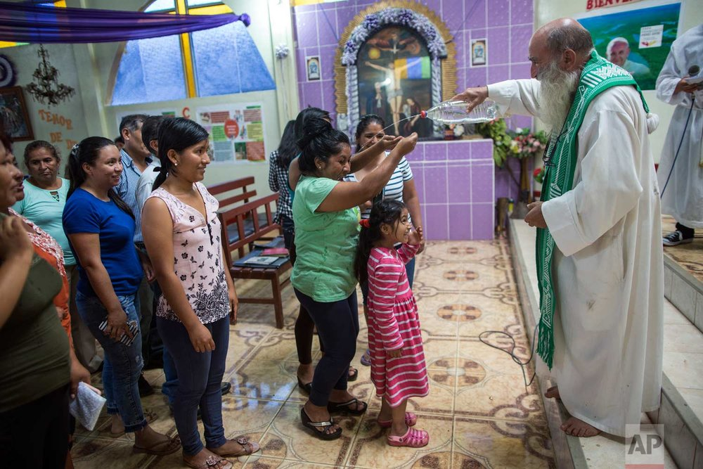 In this Jan. 14, 2018 photo, Father Pablo Zabala, better known as Padre Pablo, squirts holy water from a recycled water bottle during his last Mass as the parish priest in Boca Colorado, part of Peru's Madre de Dios region in the Amazon. (AP Photo/Rodrigo Abd)
