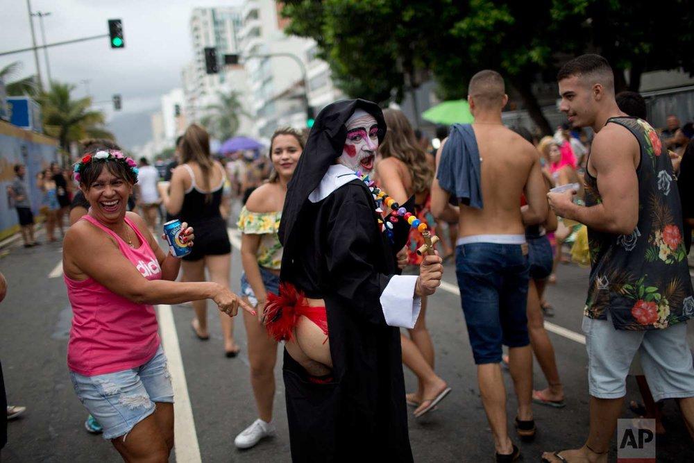 "A reveler points to the behind of a man dressed as a ""naughty nun"" at the Banda de Ipanema carnival ""bloco"" parade in Rio de Janeiro, Brazil, Saturday, Jan. 27, 2018. (AP Photo/Silvia Izquierdo)"