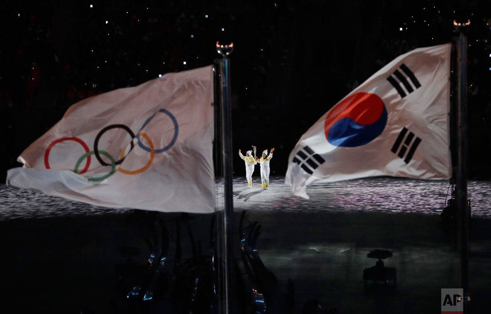 The Olympic torch is carried into the stadium during the opening ceremony of the 2018 Winter Olympics in Pyeongchang, South Korea, Friday, Feb. 9, 2018. (AP Photo/Matthias Schrader)