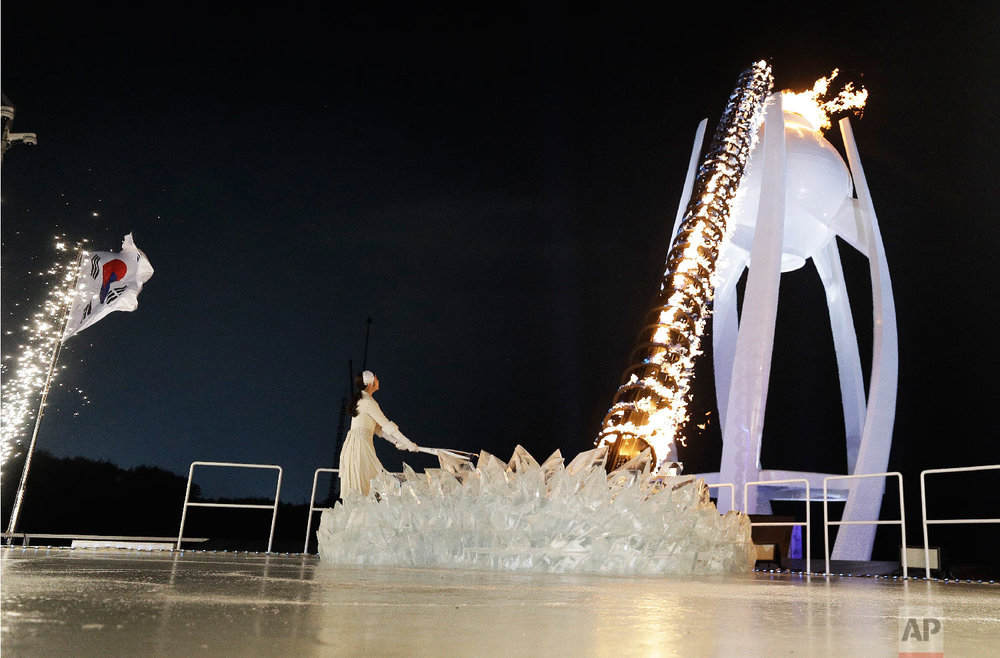 South Korean Olympic figure skating champion Yuna Kim lights the Olympic flame during the opening ceremony of the 2018 Winter Olympics in Pyeongchang, South Korea, Friday, Feb. 9, 2018. (AP Photo/David J. Phillip,Pool)