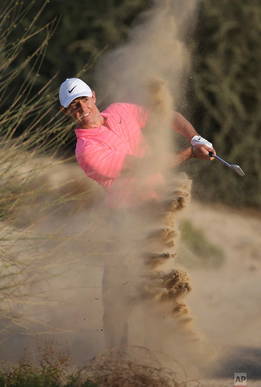 Northern Ireland's Rory McIlroy plays a shot on the dirt of the 8th hole during the second round of the Dubai Desert Classic golf tournament in Dubai, United Arab Emirates, Friday, Jan. 26, 2018. (AP Photo/Kamran Jebreili)