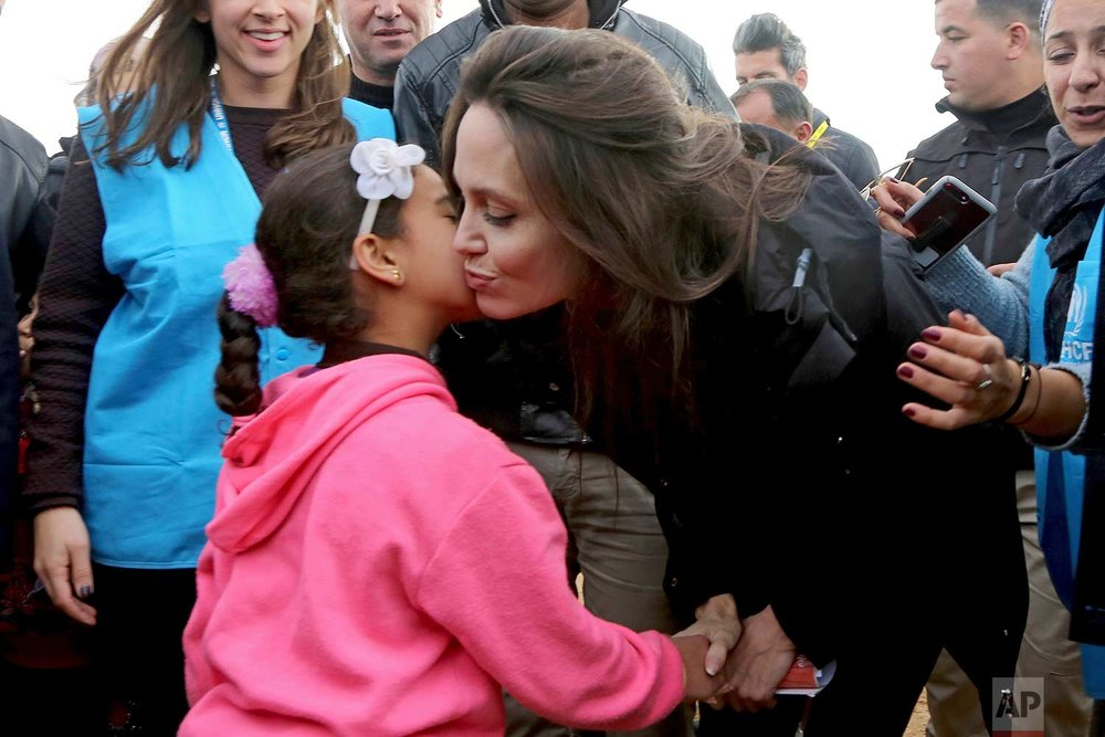 The U.N. refugee agency's special envoy, actress Angelina Jolie kisses a Syrian child during her visit to the Zaatari Syrian Refugee Camp, in Mafraq, Jordan, Sunday, Jan. 28, 2018. (AP Photo/Raad Adayleh)