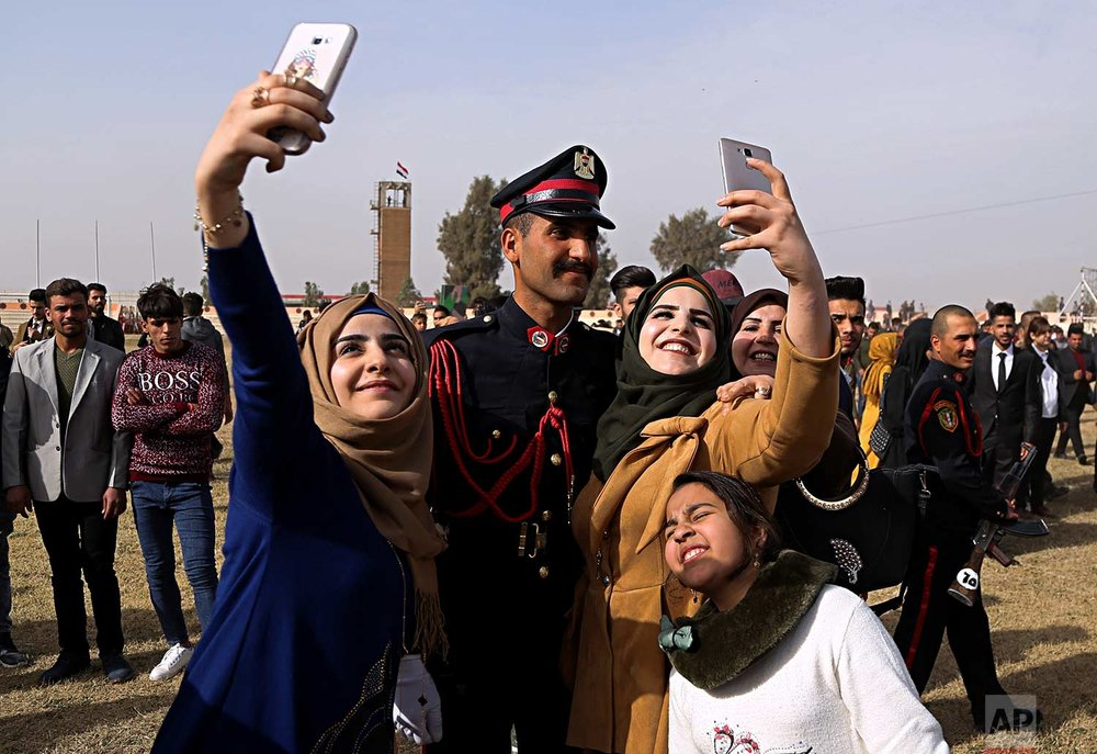 Family members of a newly graduated Iraqi Army officer take photos with him as they celebrate during Iraqi Army Day celebrations in Baghdad, Iraq, Saturday, Jan. 6, 2018. (AP Photo/Karim Kadim)
