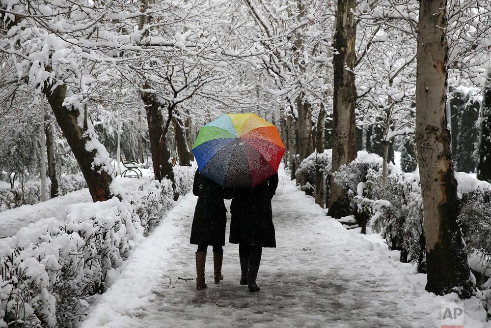 Two Iranians walk in Laleh Park in central Tehran, Iran, Sunday, Jan. 28, 2018. (AP Photo/Vahid Salemi)