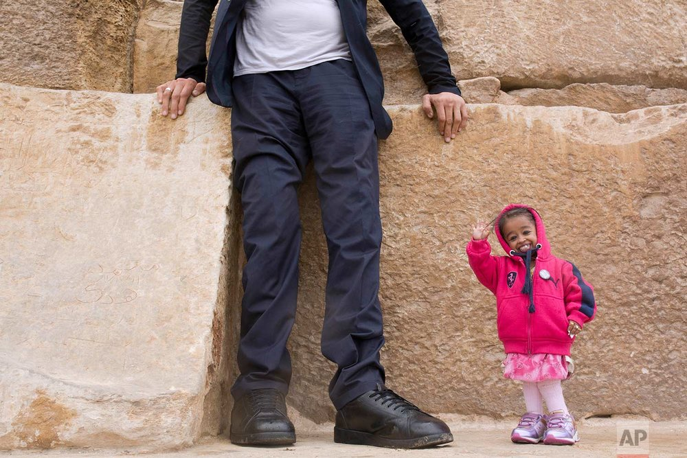 Sultan Kosen, from Turkey, 34, the tallest man on earth according to the Guinness World Records, with a height of 246.5 cm ( 8 feet 1 inch), stands on the Great Pyramid as Jyoti Amge, from India, 24, who holds the Guinness title for world's shortest woman with 62.8 cm (2 ft 06) tall, waves at the historic site of Giza Pyramids in Cairo, Egypt, Friday, Jan. 26, 2018. Both were invited by the Egyptian Tourism Promotion Board to visit Cairo's most famous sites, in an attempt to help boost tourism in Egypt. (AP Photo/Amr Nabil)
