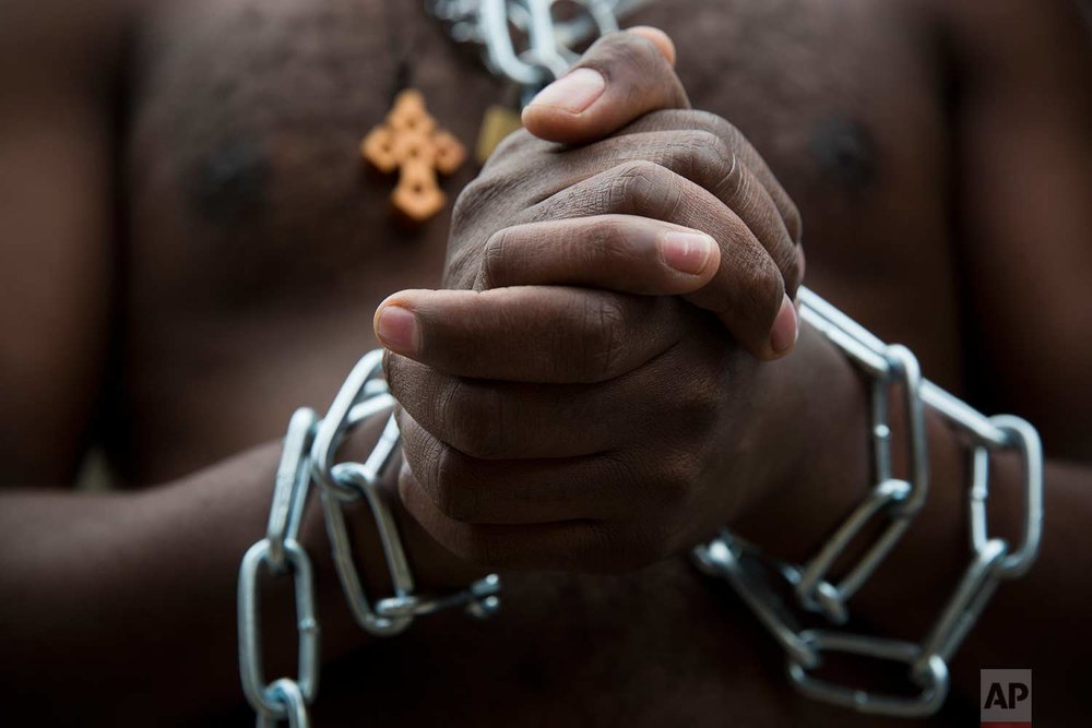 Eritrean migrants wear chains to mimic slaves at a demonstration against the Israeli government's policy to forcibly deport African refugees and asylum seekers from Israel to Uganda and Rwanda, outside the Knesset, Israel's parliament, in Jerusalem, Wednesday, Jan. 17, 2018. (AP Photo/Oded Balilty)