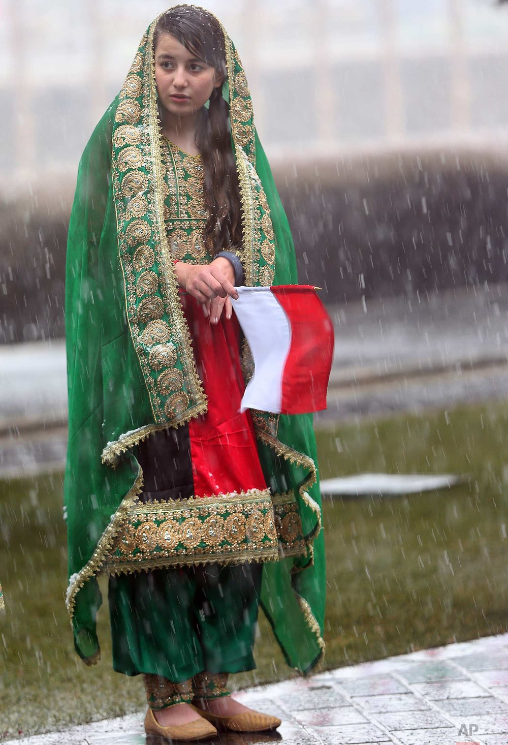 A girl holds an Indonesian flag, waiting for the Indonesian president to arrive at presidential palace in Kabul, Afghanistan, Monday, Jan. 29, 2018. (AP Photo/Massoud Hossaini)