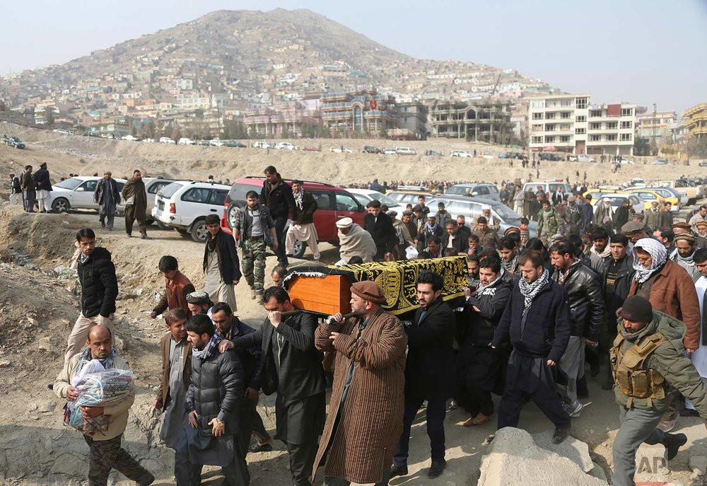 Men carry the coffin of a relative who died in Saturday's deadly suicide attack in Kabul, Afghanistan, Sunday, Jan. 28, 2018. The deadly explosion was caused by a suicide bomber driving an ambulance in the capital. (AP Photo/Rahmat Gul)